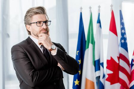 pensive diplomat in glasses touching face near flags in embassy