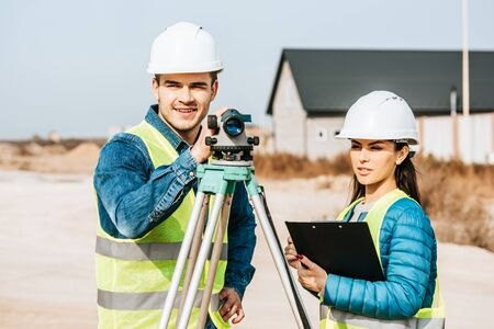 Surveyors with digital level and clipboard looking away Foto de archivo