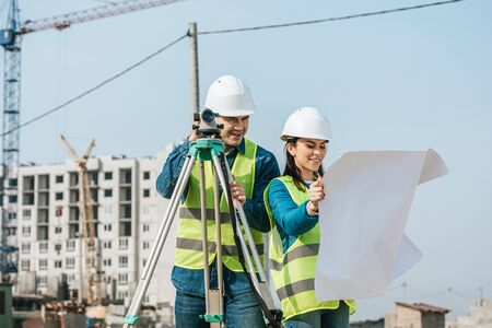 Smiling surveyors with digital level looking at blueprint on construction site