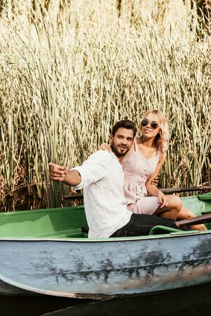 smiling man pointing with finger while sitting with girlfriend in boat near thicket of sedge Banque d'images