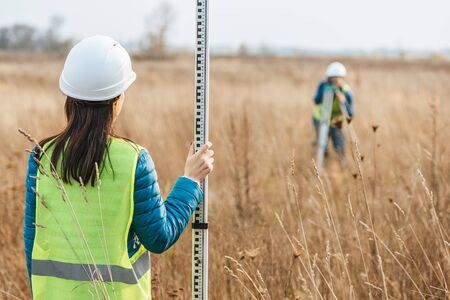 Selective focus of surveyors with survey ruler and digital level in field