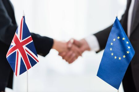 cropped view of ambassadors shaking hands near european union and united kingdom flags