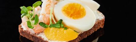 panoramic shot of rye bread with delicious shrimp near egg on smorrebrod sandwich on black Stock Photo