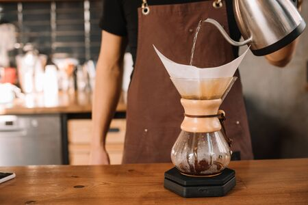 cropped view of barista preparing pour-over coffee using Chemex Coffeemaker
