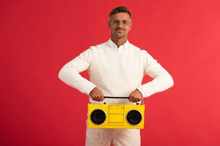 happy man in glasses holding yellow boombox isolated on red Reklamní fotografie