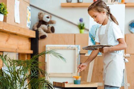 cute child in apron standing with palette and paintbrush near easel