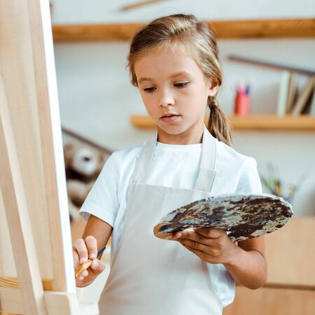 selective focus of kid in apron holding palette with colorful gouache paint and paintbrush