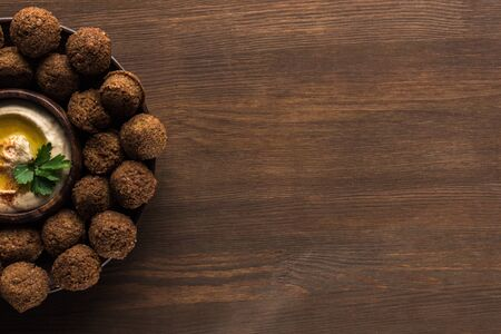 top view of falafel balls with hummus on plate on wooden table with copy space