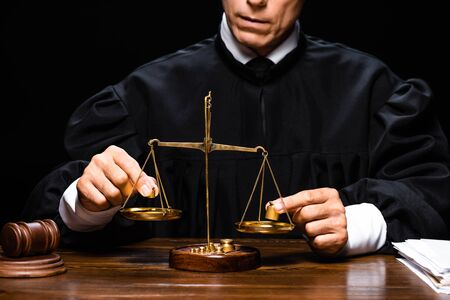 cropped view of judge in judicial robe sitting at table and holding scales of justice isolated on black 版權商用圖片