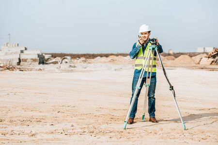 Surveyor with digital level talking on radio set on dirt road