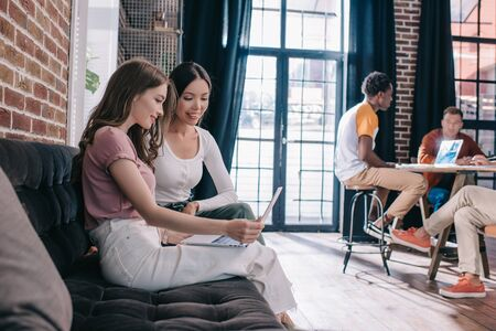 young businesswomen looking at laptop while sitting on sofa near multicultural colleagues