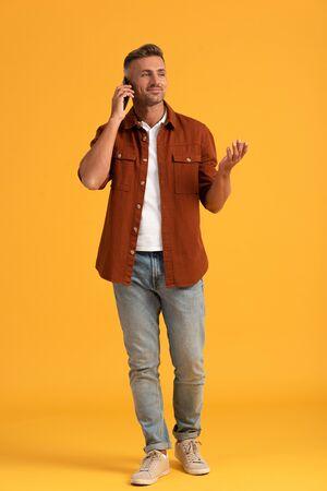 happy man gesturing while talking on smartphone and standing on orange Reklamní fotografie
