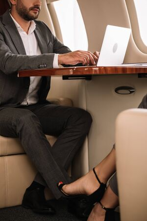 cropped view of woman sitting near bearded businessman using laptop in first class Reklamní fotografie