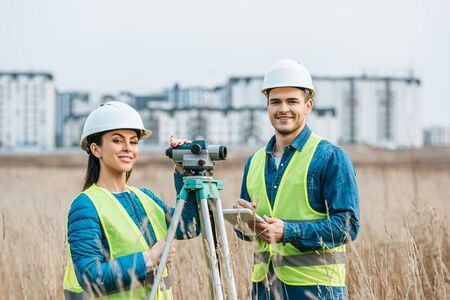 Smiling surveyors with digital level and tablet looking at camera in field