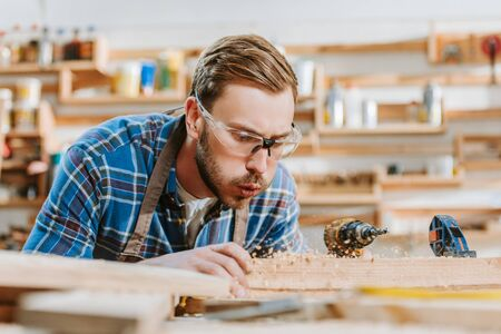 selective focus of carpenter in goggles holding hammer drill and blowing on sawdust near wooden plank