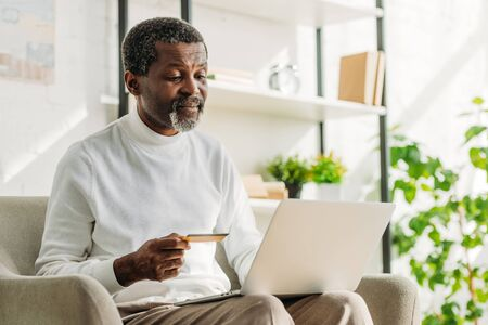senior african american man holding credit card while using laptop Reklamní fotografie