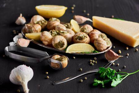 fuoco selettivo di deliziose lumache cotte con fette di limone vicino a posate, pepe nero e parmigiano su tavolo di legno nero Archivio Fotografico