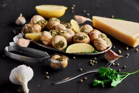 selective focus of delicious cooked escargots with lemon slices near cutlery, black peppercorn and Parmesan on black wooden table