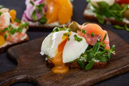 close up of danish smorrebrod sandwich with poached egg near fresh salmon on wooden cutting board 写真素材