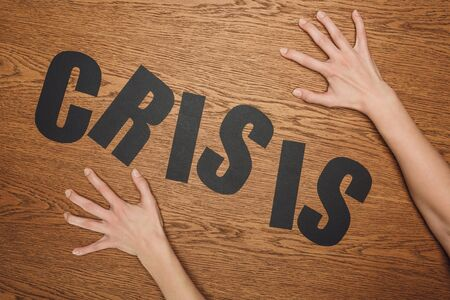 cropped view of female hands near black paper cut word crisis on wooden floor Stock Photo