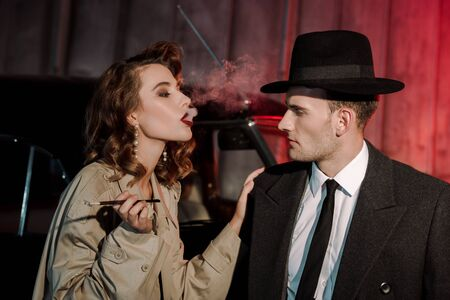 attractive woman smoking cigarette near handsome gangster in hat