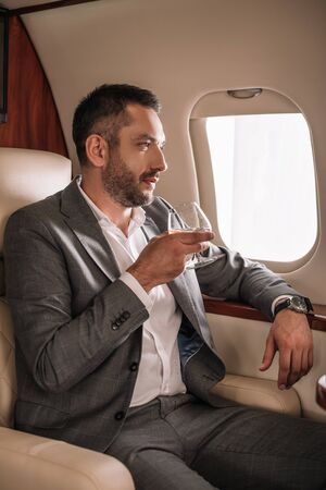 handsome businessman holding glass with cognac in private jet