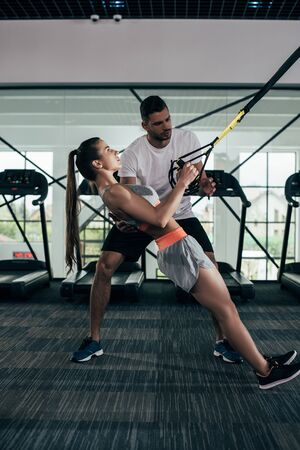 attentive trainer supporting young sportswoman working out on suspension trainer Stock Photo