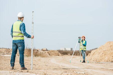Surveyors using digital level and survey ruler on dirt road