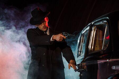 Gángster elegante sosteniendo la pistola cerca del coche retro en negro con humo