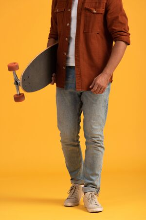 cropped view of man holding penny board on orange Banco de Imagens