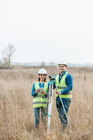 Surveyors with digital level and tablet smiling at camera in field