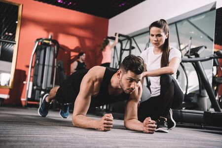 attractive trainer supervising sportsman doing plank exercise Stock Photo
