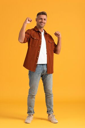 cheerful man standing with clenched fists on orange Stock Photo