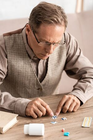 selective focus of man with alzheimer touching jigsaw with question mark