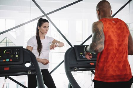 attentive trainer looking at fitness tracker while standing near african american sportsman running on treadmill Stock Photo