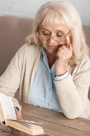 senior woman with memory loss reading book while touching glasses