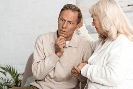 sad senior woman looking at sick husband with mental illness