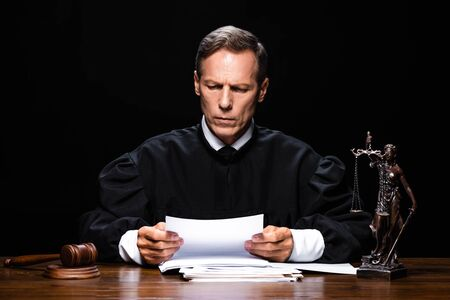 judge in judicial robe sitting at table and reading paper isolated on black 版權商用圖片