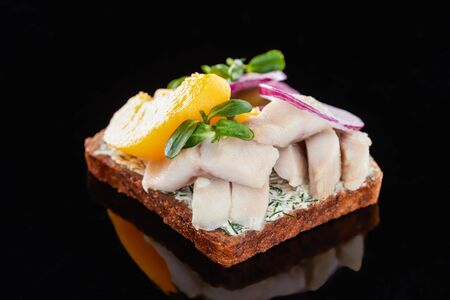 close up of herring fish and canned peaches on prepared danish smorrebrod sandwich on black 写真素材