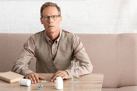 retired man with mental illness sitting near pills on table Stock Photo