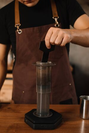 cropped view of barista preparing coffee with aeropress