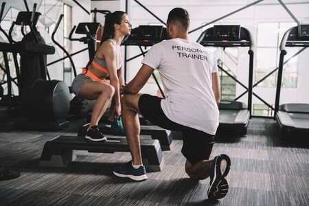 back view of personal trainer instructing young sportswoman lifting weight in gym