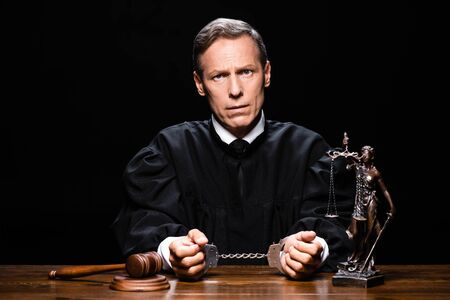 judge in judicial robe sitting at table with handcuffs isolated on black