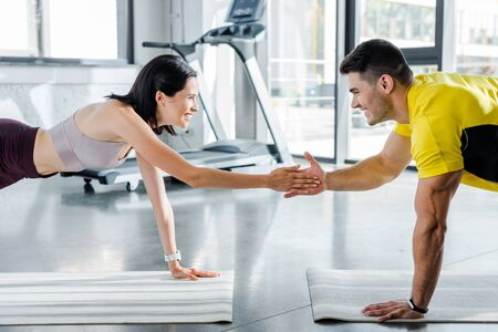 smiling sportsman and sportswoman doing plank and clapping on fitness mats in sports center