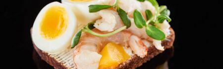 panoramic shot of shrimps on tasty smorrebrod sandwich on black
