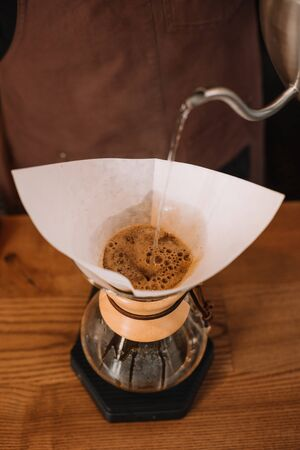 partial view of barista preparing pour-over coffee using Chemex Coffeemaker