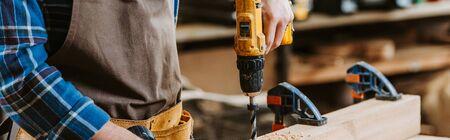 Foto panorámica de carpintero en delantal sosteniendo un taladro percutor cerca de la plancha de madera