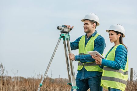 Surveyors with with digital level and tablet in field