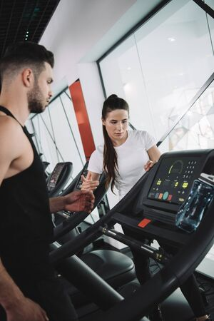 attractive trainer instructing young sportsman standing on treadmill
