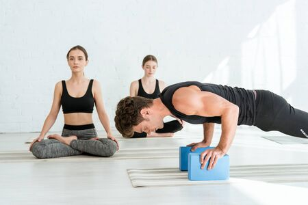 young man practicing low push up plank pose on stands, and women sitting in half lotus pose 스톡 콘텐츠